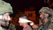 Soldado esposando y vendando los ojos a un joven palestino